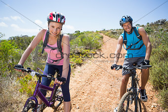 Fit couple cycling down mountain trail smiling at camera