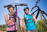 Fit couple walking down trail smiling at camera holding mountain bikes