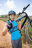 Fit man walking down trail holding mountain bike smiling at camera