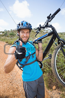 Fit man walking down trail holding mountain bike smiling at camera