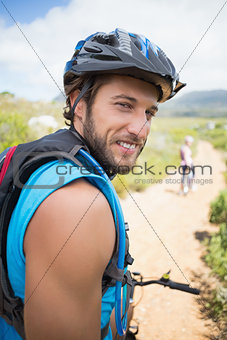 Fit couple cycling on mountain trail man smiling at camera