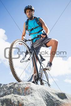 Fit man cycling on rocky terrain