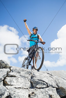 Fit man cycling on rocky terrain and cheering