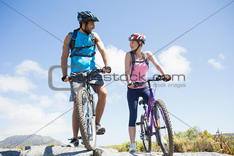 Fit cyclist couple taking a break on rocky peak smiling at each other