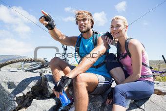 Fit cyclist couple taking a break on rocky peak