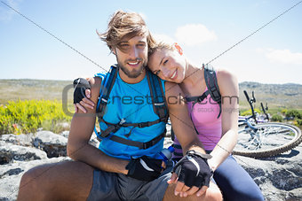 Fit cyclist couple taking a break on rocky peak smiling at camera