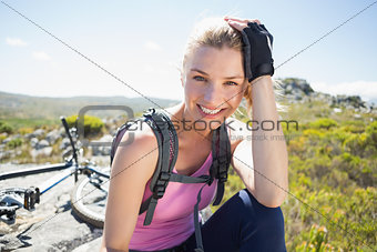 Fit pretty cyclist taking a break on rocky peak smiling at camera