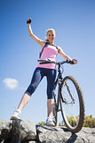 Fit pretty cyclist on a rocky terrain smiling at camera
