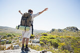 Hiker standing at the summit with arms outstretched