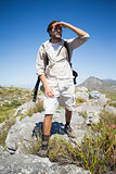 Handsome hiker standing at the summit looking around