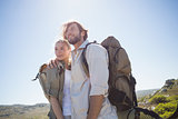 Hiking couple standing on mountain terrain smiling