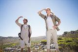 Hiking couple standing on mountain terrain looking around