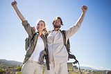 Hiking couple standing on mountain terrain cheering