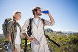 Hiking couple standing on mountain terrain taking a break