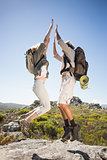 Hiking couple standing on mountain terrain cheering and jumping