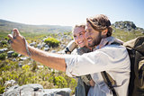 Hiking couple standing on mountain terrain taking a selfie