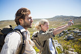 Hiking couple standing on mountain terrain taking a selfie