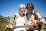 Hiking couple walking on mountain terrain looking at map