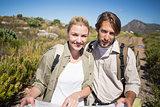 Hiking couple walking on mountain terrain holding map smiling at camera