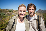 Hiking couple walking on mountain terrain smiling at camera