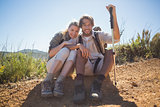 Hiking couple taking a break on mountain terrain smiling at camera