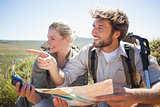 Hiking couple taking a break on mountain terrain using map and compass