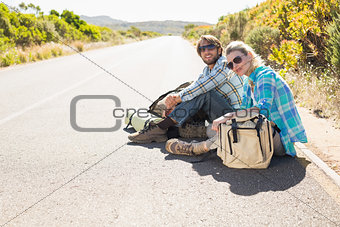 Attractive couple sitting on the road waiting for a lift