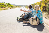 Attractive couple sitting on the road hitch hiking