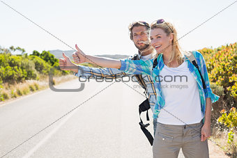 Attractive couple standing on the road hitch hiking