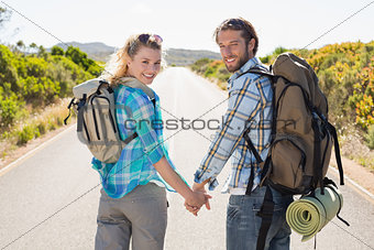 Attractive couple standing on the road holding hands smiling at camera
