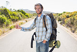 Attractive man hitch hiking on rural road