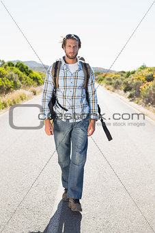 Attractive man walking on rural road