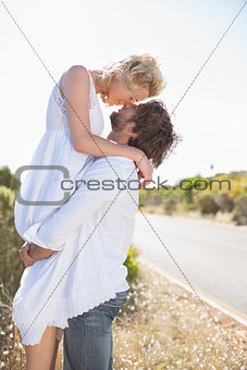Attractive man lifting up his pretty girlfriend