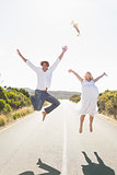 Attractive couple jumping with arms raised on the road