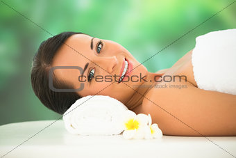 Beautiful brunette relaxing on massage table smiling at camera