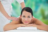 Beautiful brunette enjoying a back massage smiling at camera