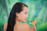 Beautiful nude brunette smelling lily