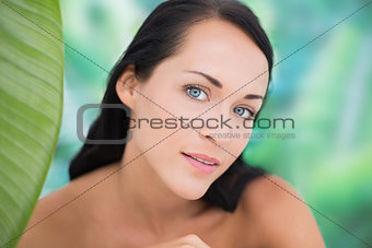 Beautiful nude brunette smiling at camera with green leaf