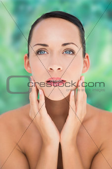 Beautiful nude brunette posing with hands on face