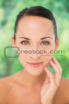 Beautiful nude brunette applying face cream