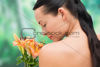 Beautiful nude brunette smelling bunch of lilies