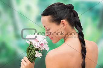 Beautiful nude brunette smelling bunch of pink flowers