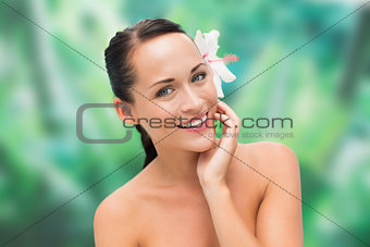 Beautiful nude brunette smiling at camera with flower in her hair