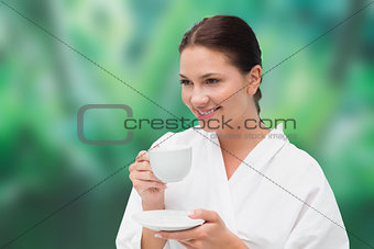 Beautiful brunette in bathrobe drinking herbal tea