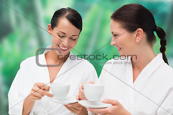 Beautiful friends in bathrobes drinking herbal tea