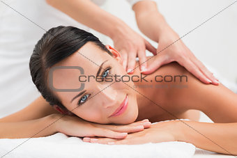 Beautiful brunette enjoying a shoulder massage smiling at camera