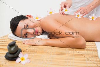 Beautiful brunette enjoying a flower back massage