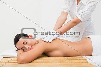 Beautiful brunette enjoying an exfoliating back massage