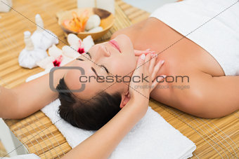 Smiling brunette enjoying a head massage