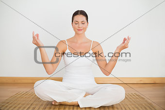Smiling brunette sitting in lotus pose looking at camera